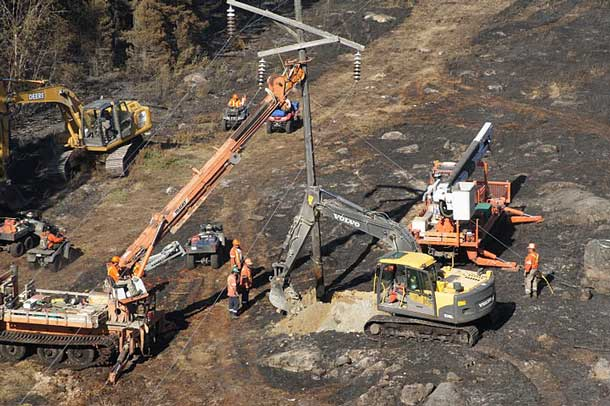 Hydro One crews work to rebuild 80 transmission structures damaged by a forest fire in northwest Ontario