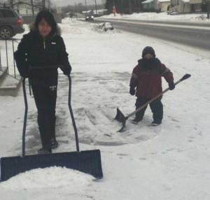 Laureen and Darius shovel the snow