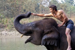 Biggest & Baddest star Niall McCann at the river with his domestic elephant in Nepal. A supreme athlete and biologist, Niall is James Bond/Tarzan and Indiana Jones rolled into one. He will ride this elephant into the jungle to discover huge rare prehistoric-looking Asian elephants.