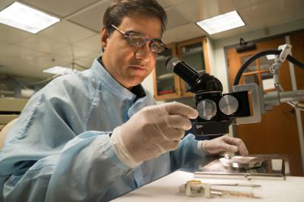 Using a binocular microscope, Dartmouth geochemist Mukul Sharma examines impact-derived spherules that he and his colleagues regard as evidence of a climate-altering meteor or comet impact 12,900 years ago. Photo Credit: Eli Burakian