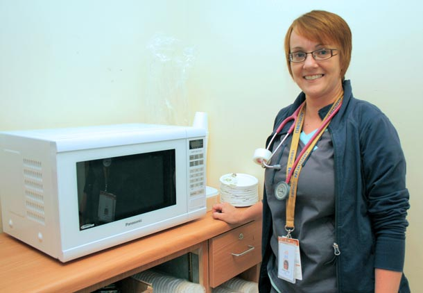 Emergency Department nurse Melanie Banfield with the D-Side Kitchen's new microwave. Patients and family members can use it to heat up coffee, soup, and other items to make their wait more comfortable.