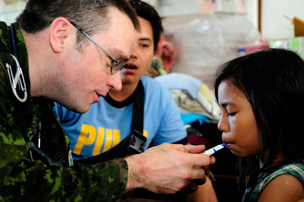Captain Ian Schoonbaert, a Doctor from the Disaster Assistance Response Team (DART) checks a local Philippian child in a refuge camp out side of Roxas city on November 16, 2013 after the area was devastated by Typhoon Hailan, one of the largest typhoons on record. Corporal Darcy Lefebvre, Canadian Forces Combat Camera Photographer