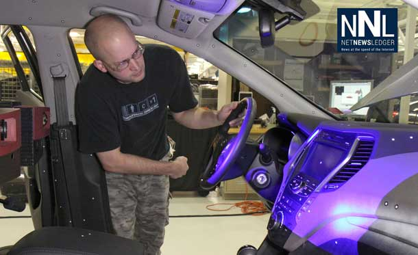 Mike Marvin from General Motors' Competitive Benchmarking team uses a blue light scanner to capture precise 3-D images of a competitive vehicle interior. Complete sets of scans become reverse-engineered computer models for comparison to GM designs.