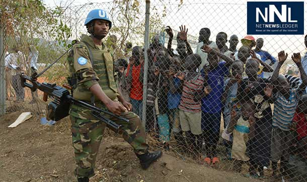A peacekeeper stands guard at UN House while displaced children look on behind a fence. UN Photo/Isaac Billy