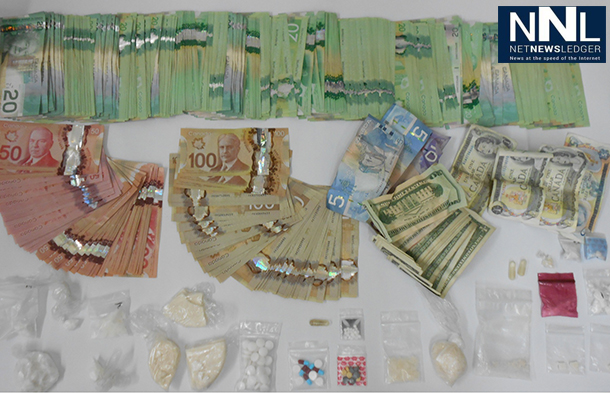 RCMP in Alberta show the cash and drugs seized in a raid in Grimshaw.