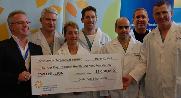 "(from right) Doctors David Puskas, Peter Clark, Jubin Payandeh, Kurt Droll, Tracy Wilson and Claude Cullinan presenting their surgeon group's donation to Foundation Board Director Clint Harris to fund a local orthopedic research program - money they hope will inspire other donations to research. ""We are looking for our community and government people to step up and say, if our surgeons are committed enough to the point of giving $30,000 each for 10 years to research to improve local healthcare problems, we should be committed too,"" said Dr. Puskas."