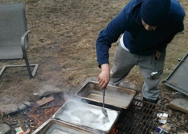 Stirring the sap to boil it down to the tasty maple syrup - Photo by Raili Alexander.