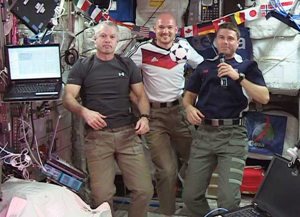"(From left) Expedition 40 Commander Steve Swanson and Flight Engineers Alexander Gerst and Reid Wiseman wish soccer fans and the World Cup 2014 ""peaceful games."" Image Credit: NASA TV"
