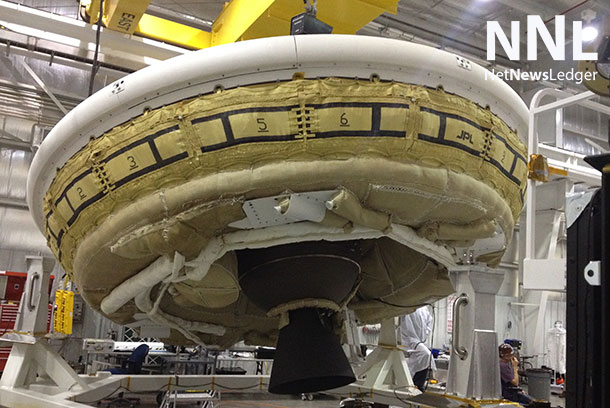 "A saucer-shaped test vehicle holding equipment for landing large payloads on Mars is shown in the Missile Assembly Building at the US Navy's Pacific Missile Range Facility in Kaua'i, Hawaii. The vehicle, part of the Low-Density Supersonic Decelerator project, will test an inflatable decelerator and a parachute at high altitudes and speeds over the Pacific Missile Range this June. A balloon will lift the vehicle to high altitudes, where a rocket will take it even higher to the top of the stratosphere at several times the speed of sound. This image was taken during a ""hang-angle"" measurement, in which engineers set the vehicle's rocket motor to the appropriate angle for the high-altitude test. The nozzle and the lower half of the Star-48 solid rocket motor are the dark objects seen in the middle of the image below the saucer. Image Credit: NASA/JPL-Caltech"