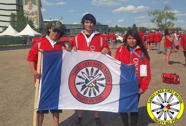 Keiron Kakepetum, Aaron Gorzen and Jurriah Kakepetum hold the SLFN flag