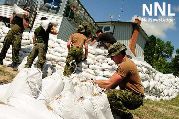Members of 2nd Battalion, Princess Patricia's Canadian Light Infantry (2PPCLI) based out of Canadian Forces Base Shilo, Manitoba, aid locals around Portage la Prairie, Manitoba in efforts to reduce damage from flooding during Operation LENTUS on July 6, 2014. Photo: Corporal Darcy Lefebvre, Canadian Forces Combat Camera