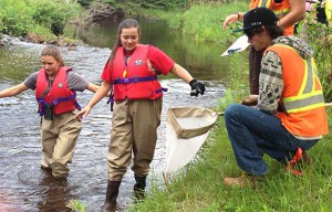 Stewardship Youth Rangers Gabrielle Gagnon (left), Jenna Langlais and Burt Buckley Collect Data and Clean Up the McIntyre River