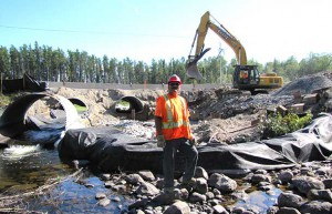 Darren Bananish stands in the bed of Creelman Creek. Behind him the culvert upgrade project proceeds apace.