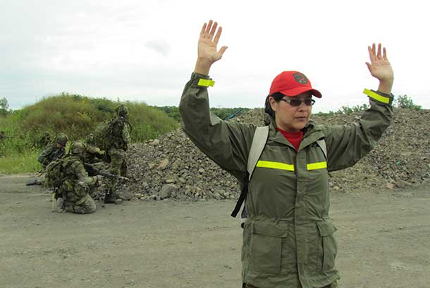 Ranger Paula Nakogee of Fort Albany keeps her hands in the air while playing the role of a prisoner of war.