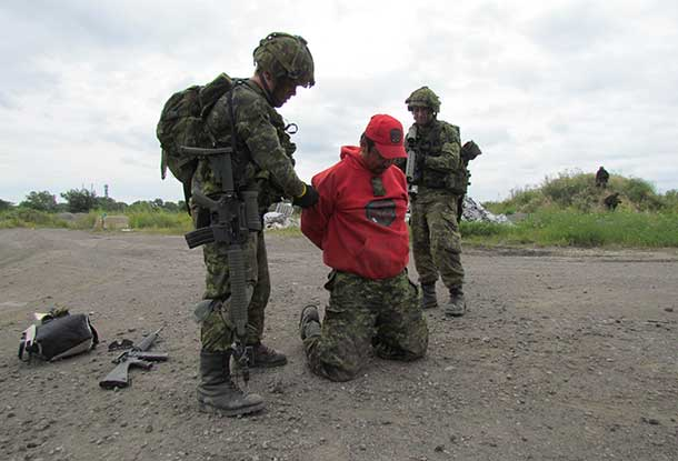 Master Corporal Leslie Anderson of Kasabonika kneels as soldiers take him prisoner.