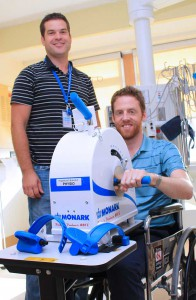 Student Mike Twigg (right) demonstrates how patients can use the new arm ergometer, purchased with a Family CARE Grant, to get much needed exercise as Mike Paularinne, Advanced Practice Physiotherapist in the ICU looks on.
