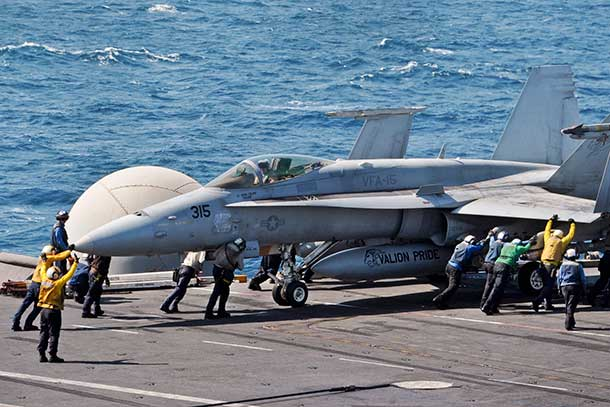 U.S. sailors guide an F/A-18C Hornet on the flight deck of the aircraft carrier USS George H.W. Bush in the Arabian Gulf, Aug. 8, 2014. The carrier is supporting maritime security operations and theater security cooperation