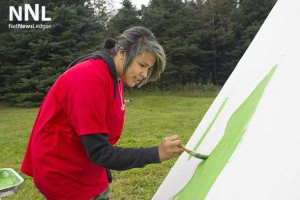 Jasmine helps paint the tee-pee at Lakehead University.