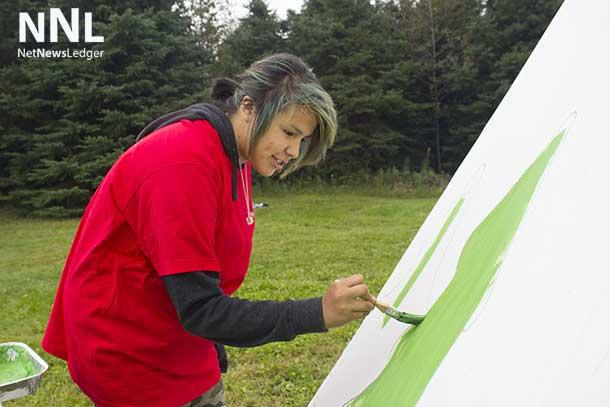 Jasmine helps paint the tee-pee at Lakehead University.