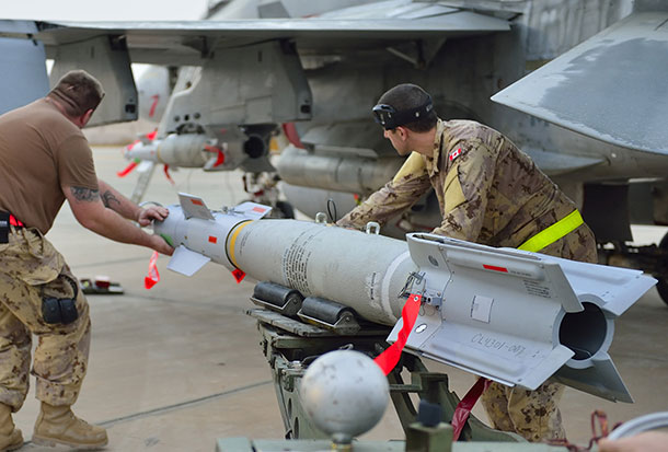 Kuwait – Royal Canadian Air Force ground crew align a bomb as they mount munitions on a CF-188 Fighter jet prior to the first combat mission over Iraq in support of Operation IMPACT. (Photo IS2014-5022-07 by Canadian Forces Combat Camera)