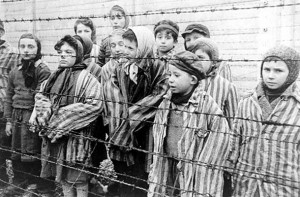 Still photograph from the Soviet Film of the liberation of Auschwitz, taken by the film unit of the First Ukrainian Front, shot over a period of several months beginning on January 27, 1945 by Alexander Voronzow and others in his group. Child survivors of Auschwitz, wearing adult-size prisoner jackets, stand behind a barbed wire fence. Among those pictured are Tomasz Szwarz; Alicja Gruenbaum; Solomon Rozalin; Gita Sztrauss; Wiera Sadler; Marta Wiess; Boro Eksztein; Josef Rozenwaser; Rafael Szlezinger; Gabriel Nejman; Gugiel Appelbaum; Mark Berkowitz (a twin); Pesa Balter; Rut Muszkies (later Webber); Miriam Friedman; and twins Miriam Mozes and Eva Mozes wearing knitted hats.