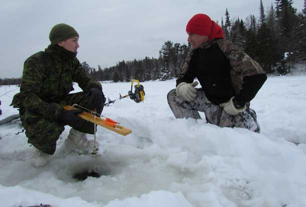 Corporal Benjamin Stephenson gets useful hints on ice fishing from Ranger Brandon Nakogee