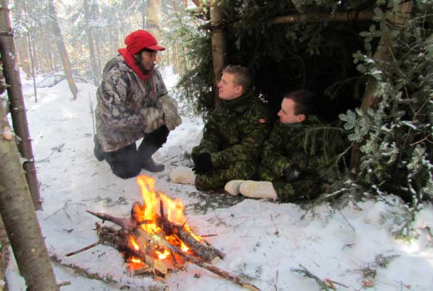 Corporal Sarah Nate, a Canadian Ranger, checks on the safety of Private Brandon Maniaci, of Smithville, and Corporal Kyle Ings, of St. Catharines, as they try out an emergency shelter during winter training