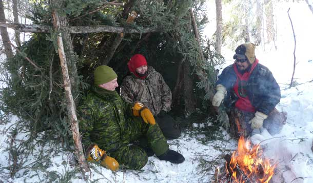Brigadier-General David Patterson tries out an improvised shelter built by two Canadian Rangers