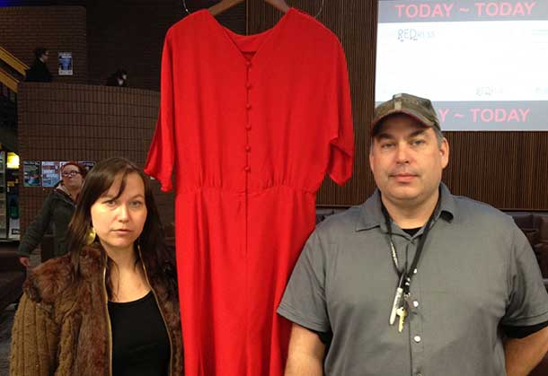 Artist Jaime Black (left) and Student Union President Chris Cartwright stand by one of over 100 red dresses displayed on campus this week.