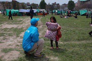 A UNICEF worker speaks to a child seeking temporary shelter at a vacant field next to Nepal's army headquarters in Kathmandu following Nepal's massive earthquake. Photo: UNICEF/NYHQ2015-1007/Nybo
