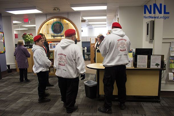 Guardian Angels getting information updates from the staff at the Brodie Street Library.