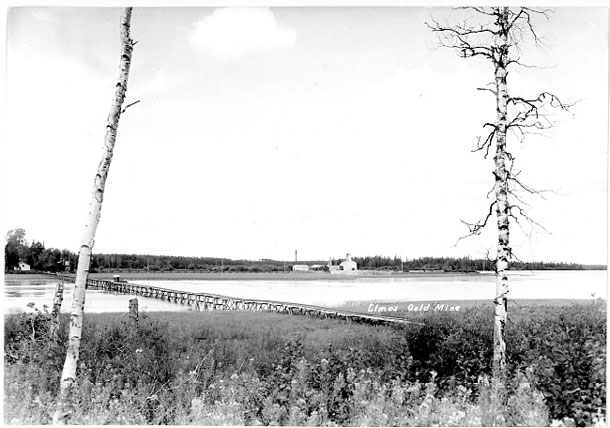 View of the mine from the mainland in 1938-39.  A light wooden bridge connected the south shore to the largest island.  The mining plant sat on a rocky islet enlarged with waste rock.