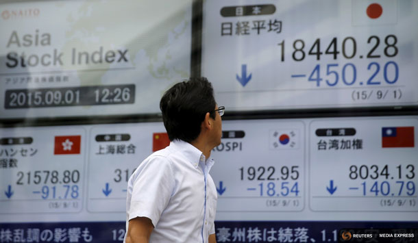 A man looks at electronic boards displaying various Asian countries' stock price indexes outside a brokerage in Tokyo, September 1, 2015. REUTERS/Toru Hanai