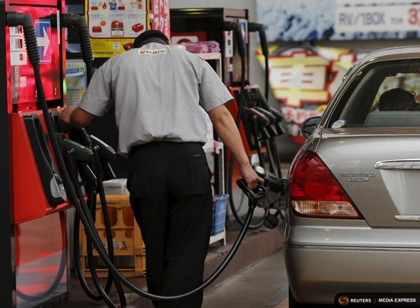 A gas station worker fuels a vehicle in Tokyo August 26, 2015. REUTERS/Toru Hanai