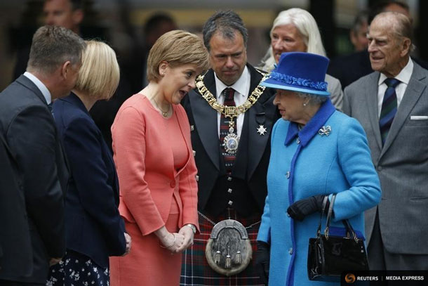 Britain's Queen Elizabeth speaks with Scotland's First Minister Nicola Sturgeon after arriving with Prince Philip (R) at Edinburgh Waverley Station, before boarding a train drawn by a steam locomotive to travel along the Scottish Borders Railway in Scotland, Britain September 9, 2015. REUTERS/Russell Cheyne