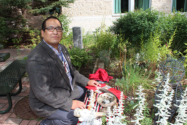 Michael Robinson, Spiritual Care Provider, TBRHSC, prepares his smudge bowl in the serene, outdoor Spirit Garden at the Thunder Bay Regional Health Sciences Centre.