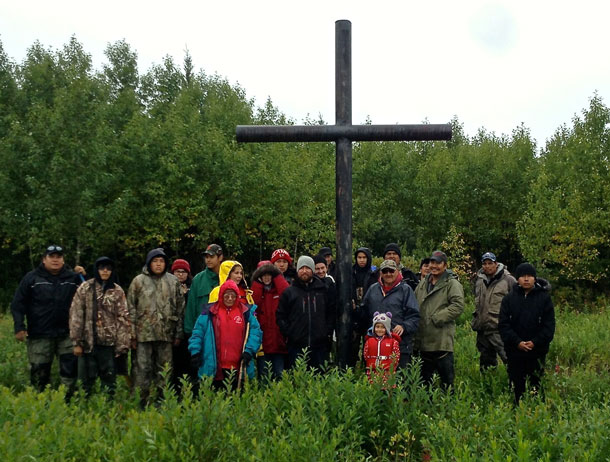 Elders, adults and youth stop at the old settlement of Winisk to say a prayer at the old cemetery before continuing home.