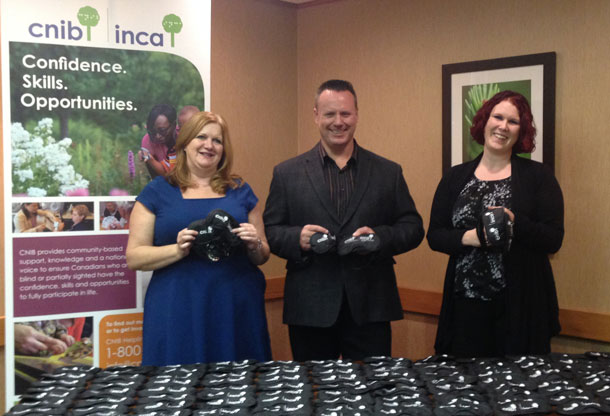 Dining in the Dark Committee Co-Chairs Dana Levanto (left) and Ashleigh Quarrell (right) stand behind 130 blindfolds with Regional Manager, Service and Operations for CNIB - North Region Rob Gaunt. Each blindfold represents 10 people who are currently accessing CNIB's programs and services.