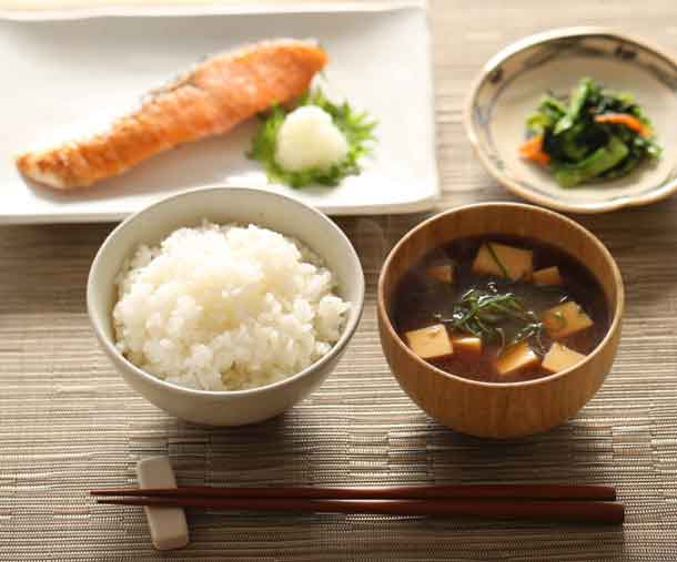 A hearty Japanese breakfast consisting of miso soup with tofu and scallions, salmon, rice and pickles. Credit: iStock kazoka30