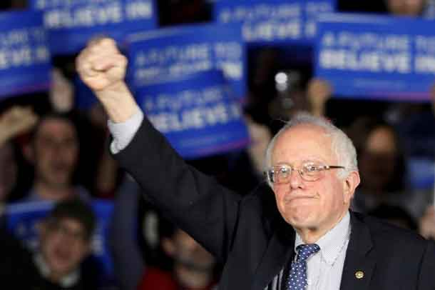 U.S. Democratic presidential candidate Bernie Sanders raises a fist as he speaks at his caucus night rally Des Moines, Iowa February 1, 2016, REUTERS/Rick Wilking