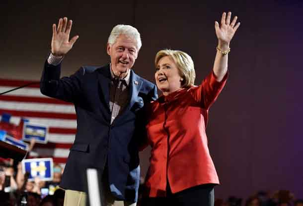 Hillary Clinton and her husband former President Bill Clinton wave to supporters after she was projected to be the winner in the Democratic caucuses  in Las Vegas. REUTERS/David Becker