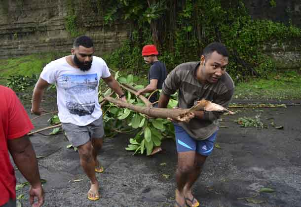 Fijian men clear a road of a fallen tree in Fiji's capital Suva after Cyclone Winston swept across Viti Levu Island, February 21, 2016. REUTERS/Taniela Qalilawa/Handout via Reuters