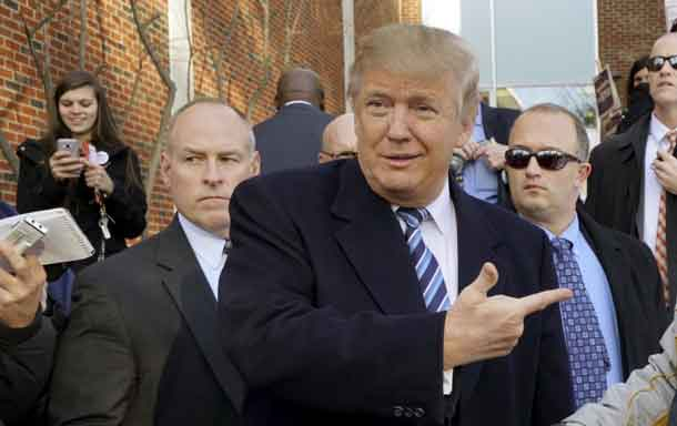 U.S. Republican presidential candidate Donald Trump points at a supporter at a polling place for the presidential primary in Manchester, New Hampshire February 9, 2016. REUTERS/Rick Wilking .