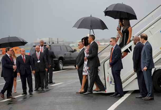 U.S. President Barack Obama and his wife Michelle approach Cuba's foreign minister Bruno Rodriguez (L) as they arrive at Havana's international airport for a three-day trip, in Havana March 20, 2016. REUTERS/Carlos Barria