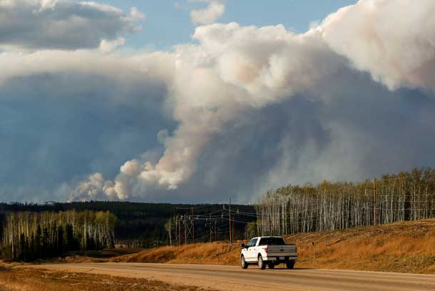 Smoke billows from the Fort McMurray wildfires as a truck drives down the highway in Kinosis, Alberta, Canada, May 5, 2016. REUTERS/Mark Blinch