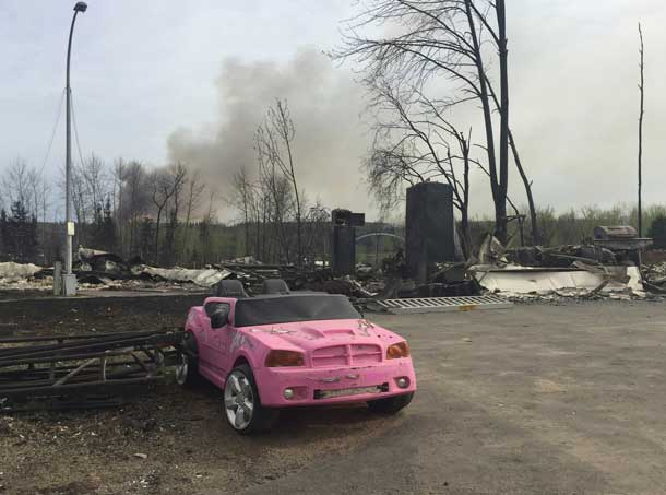 A pink car remains among the ruins of destroyed buildings after wildfires tore through the Waterways area of Fort McMurray, Alberta, Canada May 5, 2016. Courtesy of Brad Readman/Alberta Fire Fighters Association/Handout via REUTERS