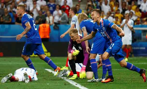 Football Soccer - England v Iceland - EURO 2016 - Round of 16 - Stade de Nice, Nice, France - 27/6/16 Iceland players celebrate as England's Joe Hart looks dejected after the game REUTERS/Kai Pfaffenbach Livepic