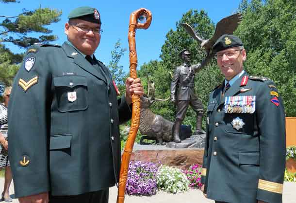 Corporal Paul Nakogee of the Algonquin Regiment, holding the regiment's eagle staff, with Lieutenant-General Marquis Hainse, commander of the Canadian Army, after a statue honouring Sergeant Francis Pegahmagabow, Canada's most highly decorated indigenous soldier, was unveiled in Parry Sound on Nationsal Aboriginal Day. Corporal Nakogee, from Attawpiskat,is studying in North Bay.
