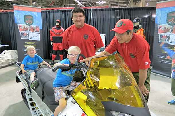Corporal Peter Echum and Sergeant Jason Roundhead with two young visitors to the Canadian Armed Forces display at the Canadian National Exhibition in Toronto`