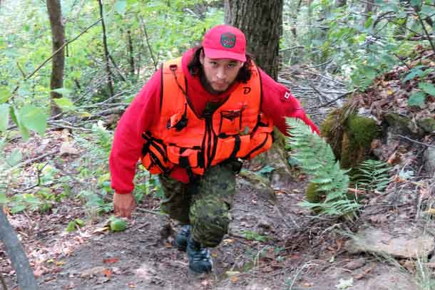 Ranger Kevin Smith nears the top of a 30-metre climb during a search and rescue exercise. credit: Sergeant Peter Moon, Canadian Rangers.